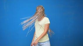 A menina na moda do moderno que agita a trançou as tranças do cabelo e o giro ao redor no fundo azul video estoque