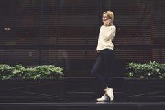 Menina na moda do moderno que está na cidade e que fala em seu smartphone Fotografia de Stock Royalty Free