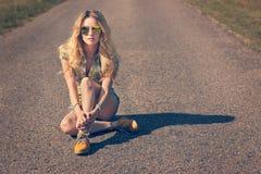Menina na moda do moderno que senta-se na estrada imagem de stock