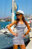 Menina na moda em um tampão do capitão no porto Foto de Stock Royalty Free