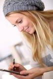 Menina na moda que toma notas no smartphone Imagens de Stock
