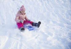 A menina na neve desliza no tempo de inverno Imagem de Stock Royalty Free