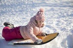 A menina na neve desliza no tempo de inverno Imagem de Stock