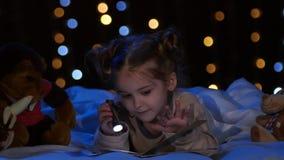 Menina na noite que lê um livro na cama Fundo de Bokeh video estoque