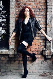 Menina na parede de tijolo vermelho velha Fotografia de Stock Royalty Free