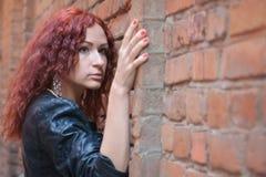 Menina na parede de tijolo vermelho velha Fotos de Stock Royalty Free