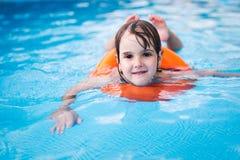 Menina na piscina com anel do flutuador foto de stock