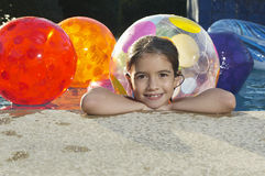 Menina na piscina com bolas de praia Foto de Stock Royalty Free