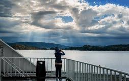 A menina na plataforma da balsa que toma imagens da paisagem do norte bonita fotografia de stock