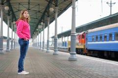 Menina na plataforma da estação de comboio imagem de stock