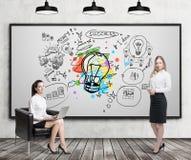 Menina na poltrona e menina loura perto do esboço colorido da ampola Fotos de Stock