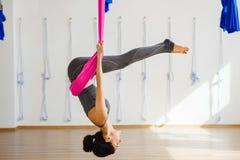 Menina na pose de cabeça para baixo da inversão na rede de seda cor-de-rosa Fotos de Stock