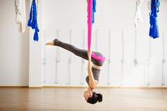 Menina na pose de cabeça para baixo da inversão na rede de seda cor-de-rosa Fotos de Stock Royalty Free