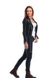 Menina na pose do casaco de cabedal que anda no fundo do estúdio quando l imagem de stock