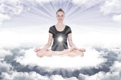 Menina na posição dos lótus da ioga sobre as nuvens entre os raios de Imagens de Stock Royalty Free