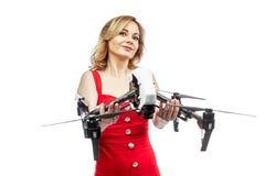 Menina na posse vermelha do vestido um quadcopter Imagem de Stock Royalty Free