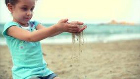 Menina na praia, bebê pequeno feliz que joga com a areia na praia Uma criança, uma criança, crianças, emoções video estoque