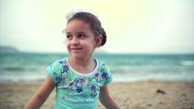 Menina na praia, bebê pequeno feliz que joga com a areia na praia Uma criança, uma criança, crianças, emoções vídeos de arquivo