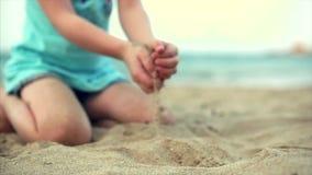 Menina na praia, bebê pequeno feliz que joga com a areia na praia Uma criança, uma criança, crianças, emoções filme