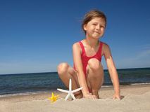 Menina na praia com starfishes fotografia de stock
