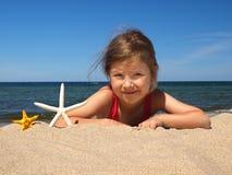 Menina na praia com starfishes imagem de stock