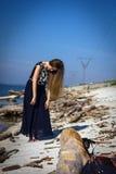 Menina na praia nos logs Imagem de Stock Royalty Free