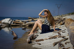 Menina na praia nos logs Imagens de Stock Royalty Free