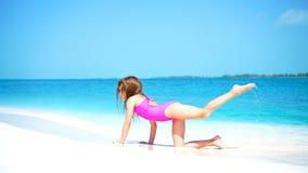 Menina na praia que tem muito divertimento na água pouco profunda na praia vídeos de arquivo