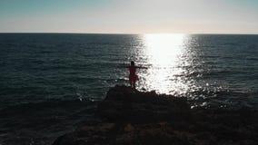 Menina na praia rochosa Posição da jovem mulher em penhascos do oceano Menina no vestido vermelho no mar Mulher atrativa que olha filme