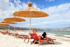 Menina na praia sob a palha Imagens de Stock Royalty Free