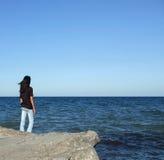 A menina na rocha olha a água Fotos de Stock Royalty Free