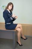 A menina na roupa azul senta-se em uma tabela no escritório Imagem de Stock Royalty Free