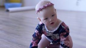 A menina na roupa bonita rasteja no assoalho nas casas em fundo unfocused vídeos de arquivo