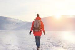 Menina na roupa brilhante e em uma trouxa que anda na neve Imagem de Stock