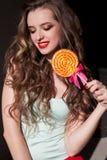 A menina na roupa colorida come o pirulito colorido saboroso Fotografia de Stock Royalty Free