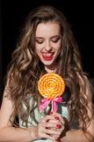 A menina na roupa colorida come o pirulito colorido saboroso Imagem de Stock Royalty Free
