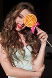 A menina na roupa colorida come o pirulito colorido saboroso Imagem de Stock