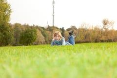 A menina na roupa das calças de brim encontra-se no gramado da grama verde no parque Fotos de Stock Royalty Free