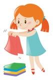 Menina na roupa de dobramento do vestido azul Imagens de Stock Royalty Free