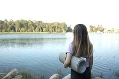 Menina na roupa do esporte que guarda uma esteira da ioga, olhando o rio fotografia de stock royalty free