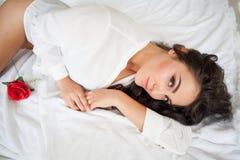 Menina na roupa interior que encontra-se em uma cama com uma rosa Fotografia de Stock Royalty Free