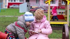 A menina na roupa morna joga com tabuleta, olhares do menino na tabuleta video estoque