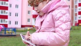 A menina na roupa morna senta-se no banco e nos jogos com a tabuleta no campo de jogos, close up, a outra menina fora de foco vídeos de arquivo