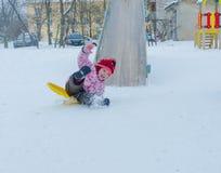 a menina na rua desliza para baixo as corrediças do gelo Imagens de Stock