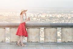 Menina na saia e no chapéu vermelhos que come o gelado Cidade da altura fotografia de stock