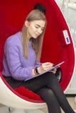 A menina na sala de estar de beleza lê e assina um contrato da manutenção imagens de stock