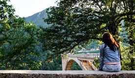 A menina na sarja de Nimes veste o assento na borda da cerca e olha o ‡ a do eviÄ do ` do urÄ do  da ponte Ä Fotos de Stock