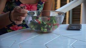 A menina na tabela come a salada vegetal dos utensílios de mesa de vidro vídeos de arquivo