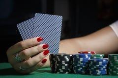 A menina na tabela do pôquer está guardando cartões Fotografia de Stock