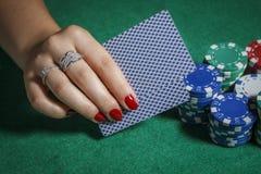 A menina na tabela do pôquer está guardando cartões Foto de Stock Royalty Free